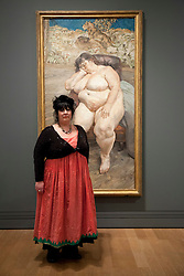 © Licensed to London News Pictures. 08/02/2012. LONDON, UK. .Sue Tilly poses in front of Lucian Frued's 'Sleeping by the Lion Carpet' a portrait of her on display at the National Portrait Gallery. .The exhibition entitled Lucian Frued Portraits, due to open on the 9th of February 2012, represents one of the largest collections the late artists work ever assembled with over 100 paintings, drawings and etchings on display. Photo credit: Matt Cetti-Roberts/LNP