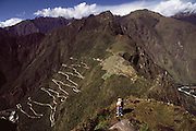 Inca ruins and switchback road leading up from the river at Machu Picchu, Peru, seen from the summit of Waynapichu. MODEL RELEASED.