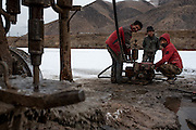 Workers monitor their machinery on the frozen crust of the Mekong river. The team is taking earth samples from the river bed in preparation for the construction of a new bridge over the Mekong in Zado, Tibet (Qinghai, China).