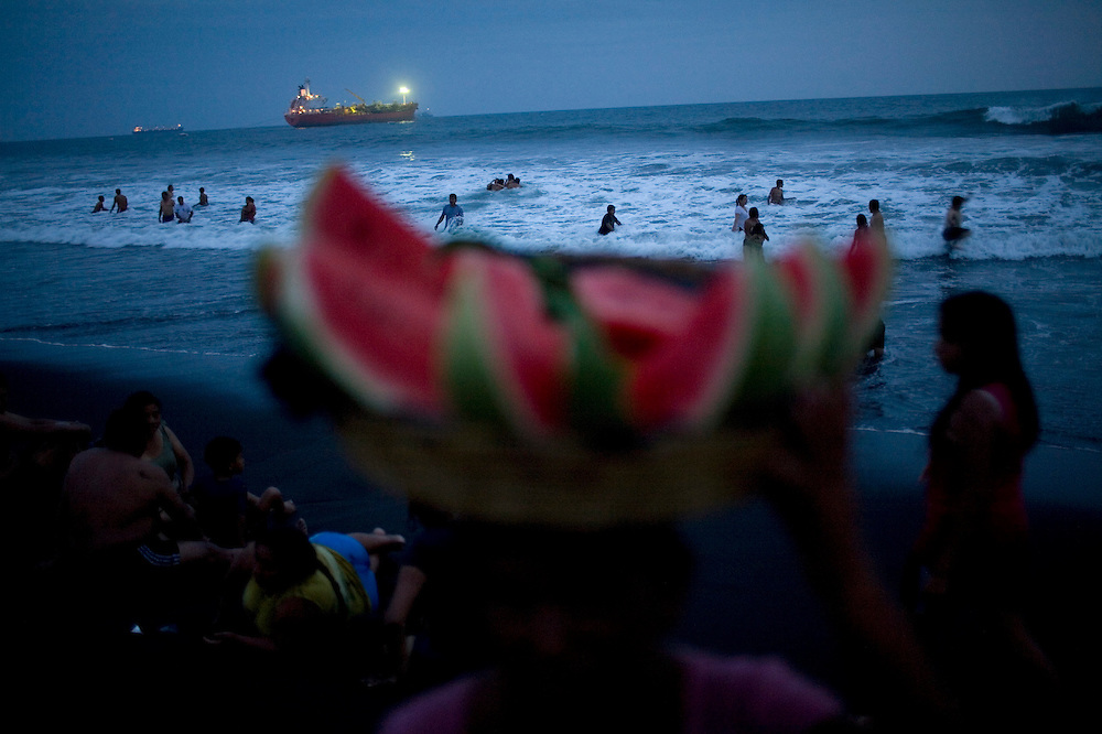 People bath at the Pacific ocean as a street vendor sell water melon at the public beach in Puerto San Jose, 60 km south from Guatemala City, Saturday, April 3, 2010. During the four day long holiday many Guatemalans visit the beach and other tourist spots.(AP Photo/Rodrigo Abd)