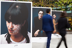 Commuters walk past Let's Talk, a photography exhibition created in partnership with Mental Health UK At Regent's Place in London. It is designed to inspire open and honest conversations about mental health by depicting each subjects' inner battles on their faces. Regents Place, Euston Road, London, October 08 2018.