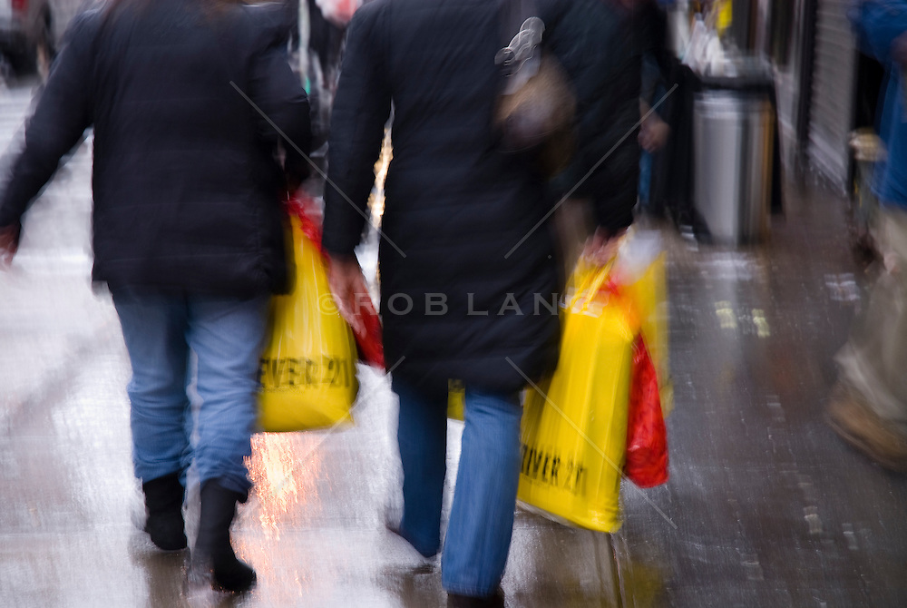 Detail of two women walking on a rainy day while carrying shopping bags