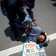 OKINAWA, JAPAN - AUGUST 19 : Anti U.S base protesters is seen being removed by police after they staged a sit-in protest protest against the construction of helipads in front of the gate of U.S. military's Northern Training Area in the village of Higashi, Okinawa Prefecture, on August 19, 2016. Japanese government resume construction of total six helipads in a fragile ten million year old Yanbaru forest that is home to endemic endangered species such as the Okinawan rail and Okinawan wood pecker. (Photo by Richard Atrero de Guzman/NURPhoto)