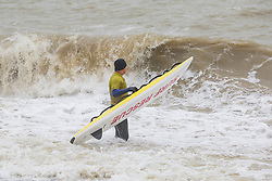 © Licensed to London News Pictures. 20/01/2018. Brighton, UK. Members of the Brighton Surf Life Saving Club (SLSC) brave the powerful waves and and wet weather to take part in their weekly training session. Photo credit: Hugo Michiels/LNP