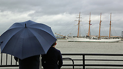 © Licensed to London News Pictures. 26/08/2015.  Sail training ship Esmerelda approaches the QEII Bridge as spectators watch from under an umbrella. The Chilean navy vessel is over 100 metres long and has four masts.  A number of tall ships have arrived in London today in rainy weather including the Chilean navy's four masted sail training ship Esmerelda. Other ships are heading to south east London for a tall ships event which is part of the Mayor of London's Totally Thames festival. Credit : Rob Powell/LNP