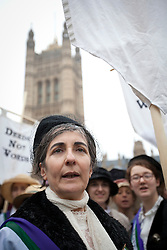 © Licensed to London News Pictures. 08/03/2013. London, UK. Dr Helen Pankhurst, the granddaughter of suffragette Sylvia Pankhurst is seen in period dress at a press call at the end of a walk to Parliament taking place on International Women's Day in London today (08/03/2013) . The end of the walk, which coincides with International Women's Day, launches poverty charity Care International's 'Walk in Her Shoes Campaign', which encourages women to put themselves the shoes of women in the developing world. Photo credit: Matt Cetti-Roberts/LNP