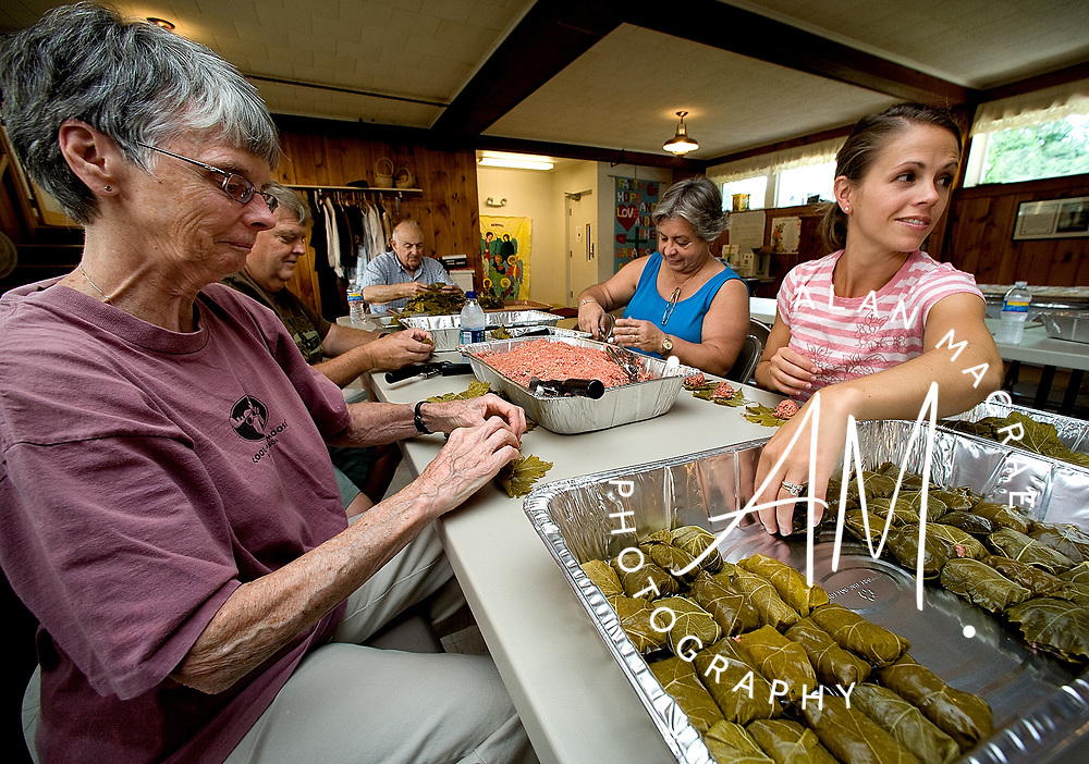 Cori Bailey, right, puts a dolmathes, a rolled grape leaf stuffed with a beef and rice filling as she and other members of the local Greek Orthodox parish prepare food for Saturday's annual Greek festival.  From the right are Mary Lou Beshta, Gus Garside, George Savramis, Mary Garside, and Bailey.  (Alan MacRae/for the Citizen)