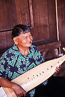 An Iban man at the Sarawak Cultural Village demonstrates  the craft of making and playing a traditional type of guitar.