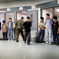 Verenigde Staten.Arizona.Nogales.juli 2005.<br /> Grenspolitie arresteert illegalen in de woestijn van Zuid Arizona, die illegaal vanuit Mexico de Verenigde Staten zijn binnengekomen. Ze worden gefoullerd op wapens en hun papieren worden gecontroleerd. Daarna worden de illegalen naar het hoofdbureau van de grenspolitie getransporteerd, waarna ze geregistreerd worden alvorens ze terug de grens overgebracht worden.<br /> Op de foto Mexicaanse illegalen in de cel op het hoofdbureau van de grenspolitie in Nogales in afwachting van hun lot.Ze wachten op hun registratie.Tussen de vele vluchtelingen zitten ook vaak criminelen, die goed doorgelicht moeten worden.Gevangenschap.Hechtenis.Gevangenis.Illegale vluchtelingen.Criminelen.Grenspolitie.Border Patrol.Identiteitscontrole.Identificatie.Uitzichtloosheid.Grensproblematiek.Grens.Mexicanen.<br /> Archives 2005. Chase by police on illegal Mexicans who cross the border in Arizona. In the border police headquarters.