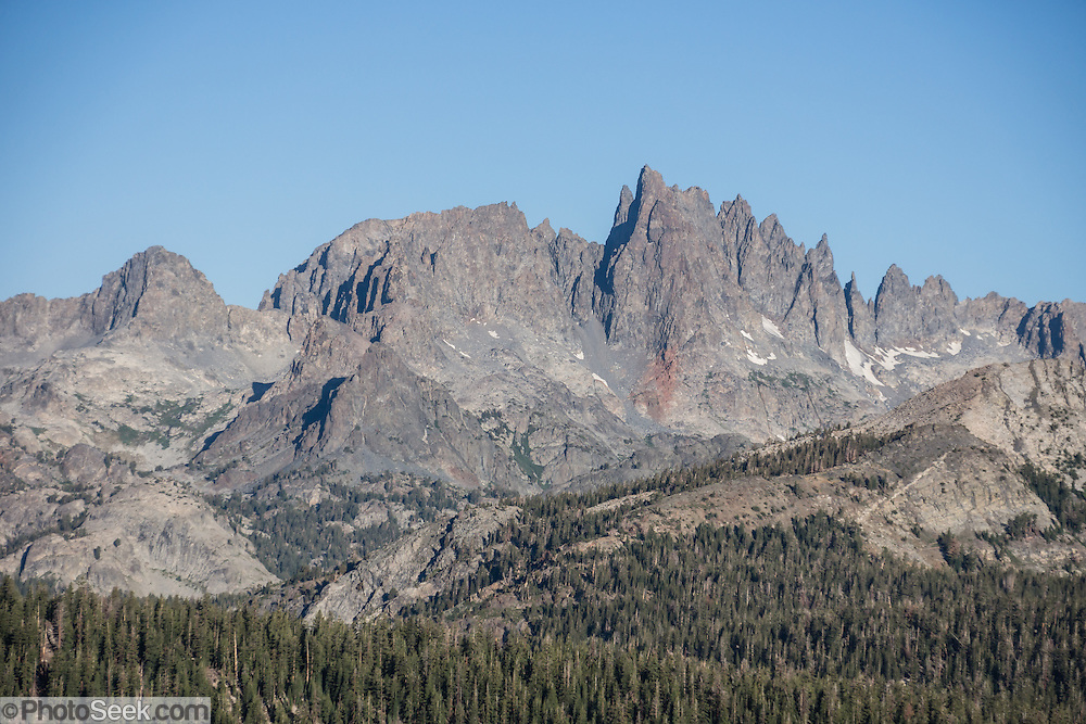From Minaret Vista, see  jagged peaks of the Ritter Range, a sub-range of the Sierra Nevada mountains, in Ansel Adams Wilderness, Inyo National Forest, California, USA. Minaret Vista is the highest driveable lookout in the Mammoth Lakes area. The Minarets are all that remains of an ancient lava flow which existed long before the formation of Sierra Nevada. The 200-million-year-old volcanic flows and welded ash of what is now the Ritter Range metamorphosed and capped a large magma chamber that later (85 million years ago) cooled into the Cathedral Peak Granodiorite (coarse-grained quartz monzonite), now exposed in impressive peaks of eastern Yosemite National Park.