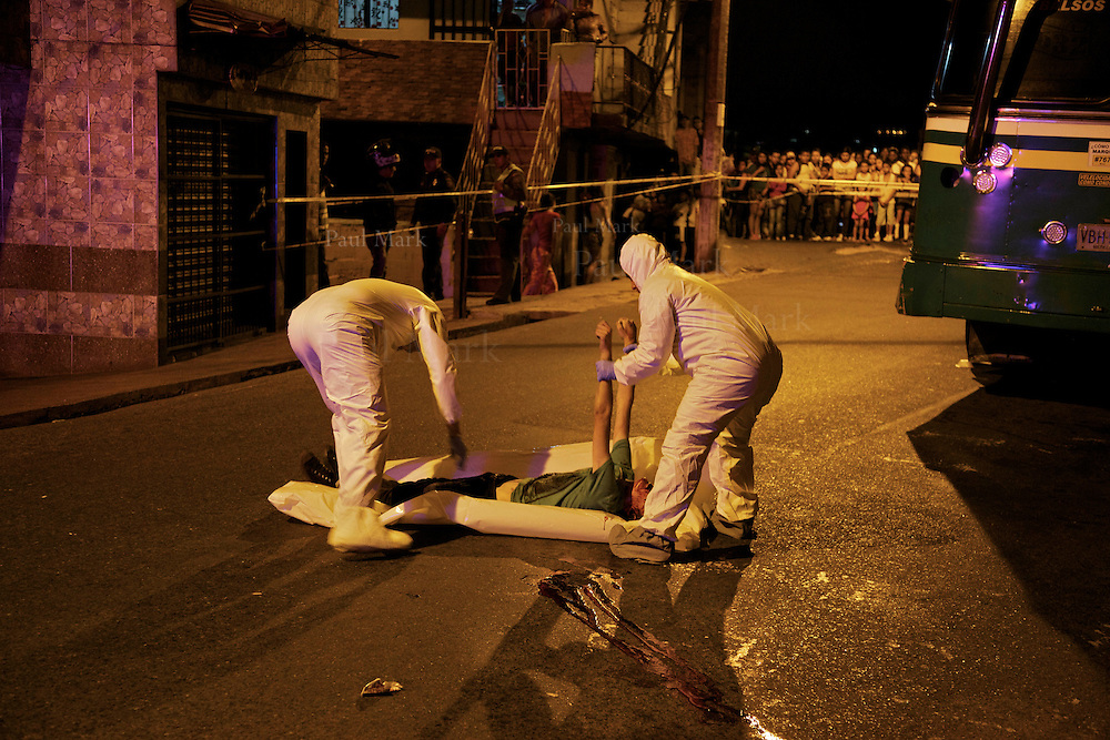 Police investigators collect the body of a 16-year-old homicide victim in the Andalucía neighborhood in Medellin's northeast.