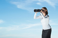 Mid-adult woman standing outside looking through large pair of binoculars