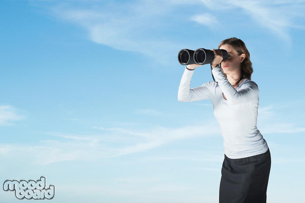 Mid-adult woman standing outside looking through large pair of binoculars