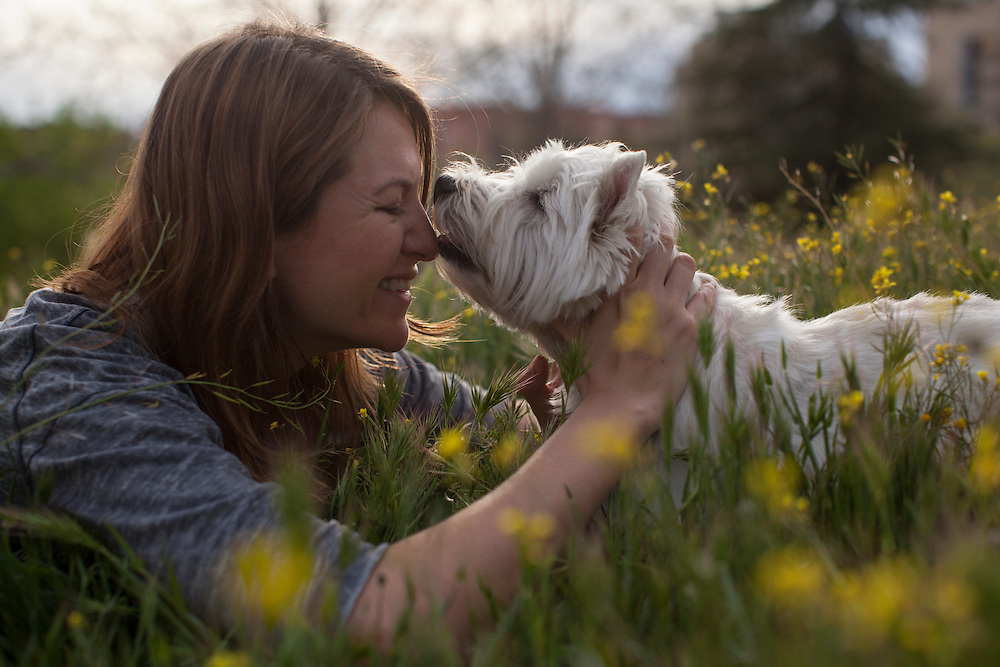Young woman playing with a westie dog in Madrid, Spain.