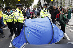 © Licensed to London News Pictures. 07/10/2019. London, UK. Extinction Rebellion protestors' tents are removed by police on Millbank near Parliament in central London . Activists will converge on Westminster blockading roads in the area for at least two weeks calling on government departments to 'Tell the Truth' about what they are doing to tackle the Emergency. Photo credit: Peter Macdiarmid/LNP