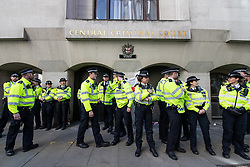 © Licensed to London News Pictures . 27/09/2018 . London , UK . Police outside the entrance to the Central Criminal Court as supporters of former EDL leader Tommy Robinson (real name Stephen Yaxley-Lennon ) gather outside the Old Bailey , as Robinson faces a retrial for Contempt of Court following his actions outside Leeds Crown Court in May 2018 . Robinson was already serving a suspended sentence for the same offence when convicted in May and served time in jail as a consequence , but the newer conviction was quashed by the Court of Appeal and a retrial ordered . Photo credit: Joel Goodman/LNP