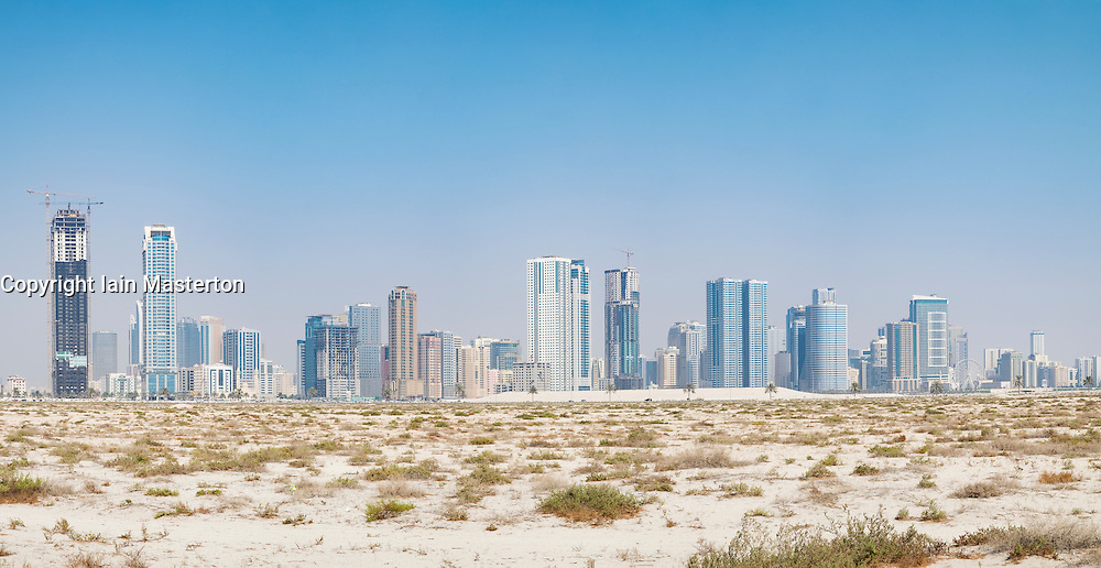 Daytime skyline view of  modern high-rise apartment buildings from desert  in Sharjah United Arab Emirates