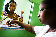 Sister Kwame Amena Catherine collects money from Konaté Fatouma at the pharmacy of the NDA health center in Dimbokro, Cote d'Ivoire on Friday June 19, 2009.