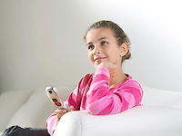Young Girl leaning on arm of sofa hand on chin holding phone daydreaming