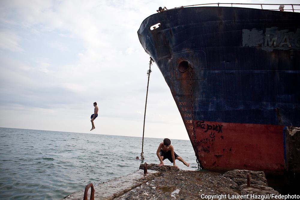 Août 2011. Abkhazie. Sukhumi. Pays indépendant non reconnu par la communauté internationale. Bâteau turque échoué depuis 15 ans en bord de plage. Les enfants jouent dessus et les pécheurs s'y installent.