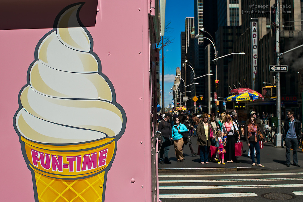 Sign on ice cream truck and crowd waiting to cross street