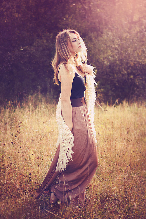 A beautiful  young woman with blonde hair walking outside in the nature wearing a long brown skirt and a crochet stole
