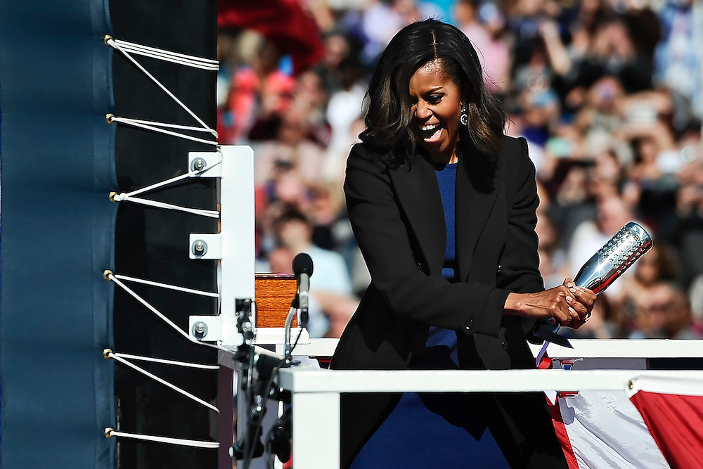 First lady Michelle Obama christens the USS Illinois with a bottle of sparkling wine at Electric Boat, a division of General Dynamics, shipyard, Saturday, in Groton, Conn. (AP Photo/Jessica Hill)