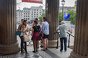 Tourists in the foreground with German artist Katharina Fritsch's sculpture 'Hahn/Cock', a 4.72m high scale fibre glass and polyester resin, ultramarine blue domestic cockerel, just unveiled on the fourth plinth in the north-west corner of Trafalgar Square, London. The 4th plinth was intended to hold a statue of William IV, but remained bare due to low funds. In 1999, a sequence of three contemporary artworks to be displayed on the plinth were announced.