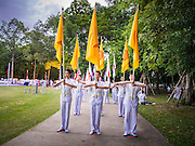 19 JULY 2014 - KHLONG LUANG, PATHUM THANI, THAILAND:  Lay people lead a procession around the ordination hall at Wat Phra Dhammakaya during an ordination ceremony. Seventy-seven men from 18 countries were ordained as Buddhist monks and novices at Wat Phra Dhammakaya, a Buddhist temple  north of Bangkok, Saturday. It is the center of the Dhammakaya Movement, a Buddhist sect founded in the 1970s and led by Phra Dhammachayo (Phrathepyanmahamuni). It is the largest temple in Thailand. The Dhammakaya sect has an active outreach program that attracts visitors from around the world.   PHOTO BY JACK KURTZ