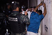 Military Police on an operation to find gang members, search three men loitering in a park. 12th August 2017.