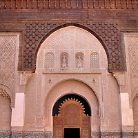 Medersa Ben Youssef Main Courtyard in Marrakech, Morocco<br /> Marinid ruler Ali Ben Youssef founded a madrasa in Marrakech during his reign over Morocco from 1488 through 1458. The primary mission of the theological college was to teach the Quran but other subjects were also taught. The current Medersa Ben Youssef structure was commissioned by Sultan Sidi Abdallah al-Ghalib and finished in 1564. The building&rsquo;s architectural highlight is the 49 by 65 foot, central courtyard. At the south end is this entrance to the prayer hall.  The doorway is decorated with several horseshoe arches, zellij tiles, marble columns, mashrabiya screens, etched plasterwork and carved cedar.