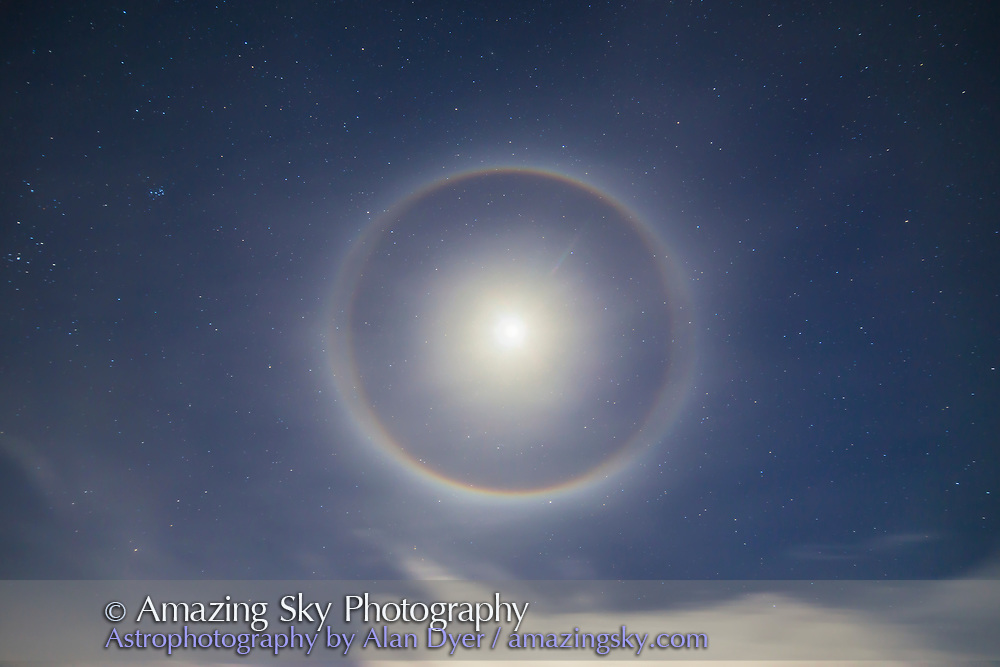 An ice crystal halo around the waxing quarter Moon, Dec. 1, 2014, taken from New Mexico. This is a 30-second exposure at f/2.8 with the 14mm lens and Canon 6D at ISO 400, with the bright area around the Moon itself masked and made from 3 shorter exposures to lower the intensity of the centre of the halo. The altitude of the Moon was 62° and the halo shows a split appearance on the east and west sides from what is called a circumscribed halo adding to the normal 22° halo.
