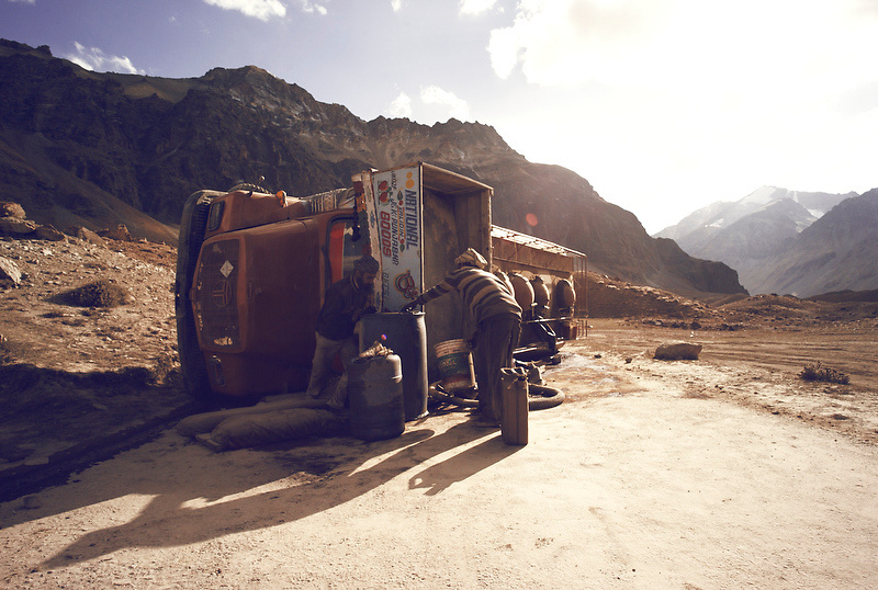 Two men siphon off fuel from an overturned truck outside the tent camp of Sarchu, Ladakh, India on Sep 9, 2007.
