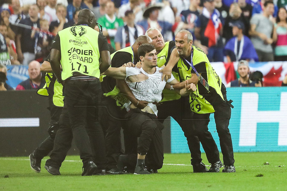 Supporter being detained by stewards at the final match between France and Portugal. Portugal won the Euro Cup beating in the final home team France at Saint Denis stadium in Paris, after winning on extra-time by 1-0.