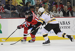 Apr 10; Newark, NJ, USA; New Jersey Devils right wing Vladimir Zharkov (18) skates with the puck while being defended by Boston Bruins defenseman Andrew Ference (21) during the second period of their game at the Prudential Center.