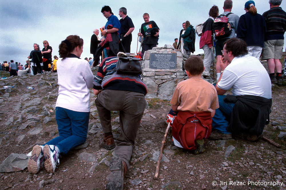 IRELAND CO. MAYO CORAGH PATRICK JUL99 - A group of pilgrims kneel and pray on top of Croagh Patrick mountain in western Ireland. Around 25,000 people, some of which are bare-footed, participate in this pilgrimage to the top of Croagh Patick mountain on the last Sunday of July from where in 441 A.D. St. Patrick supposedly sent Ireland's reptiles to their doom. ..jre/Photo by Jiri Rezac..© Jiri Rezac 1999..Contact: +44 (0) 7050 110 417.Mobile: +44 (0) 7801 337 683.Office: +44 (0) 20 8968 9635..Email: jiri@jirirezac.com.Web: www.jirirezac.com..© All images Jiri Rezac 1999 - All rights reserved.