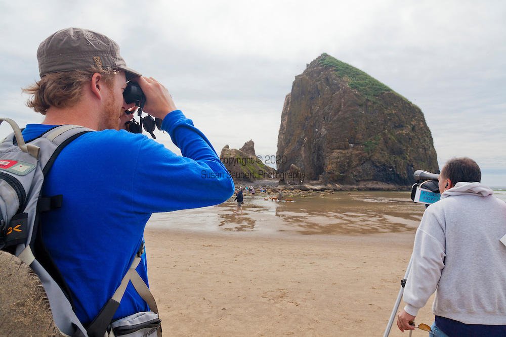Exploring the tide pools at low tide at Haystack Rock, Cannon Beach, Oregon.  Haystack Rock, located to the southwest of downtown Cannon Beach, near Tolovana Park. This igneous rock has an elevation of 235 feet, and is often accessible at low tide, especially in the summertime. The rock is also protected as a marine sanctuary, Oregon Islands National Wildlife Refuge, and events are not allowed within 100 feet of either side of the rock. Near Haystack Rock are the Needles, two tall rocks rising straight out of the water.