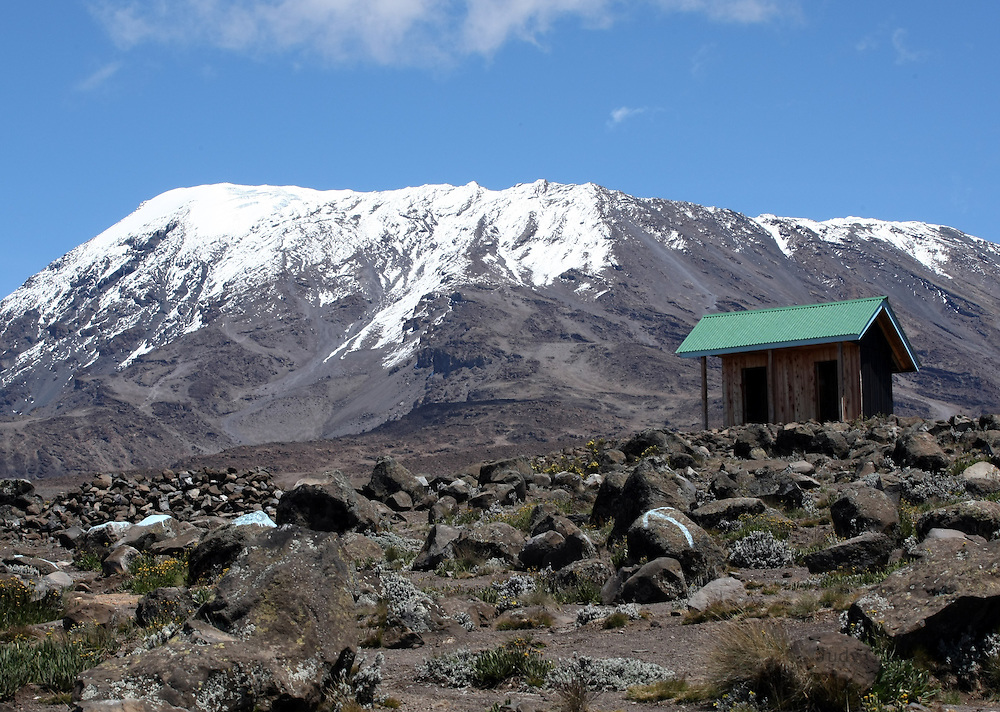 The final destination in site, the summit of the majestic Mt. Kilimanjaro looms over a tiny WC hut.
