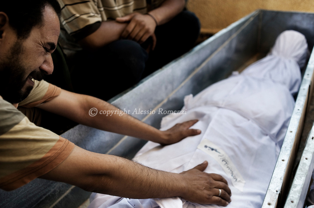 LIBYAN ARAB JAMAHIRIYA, Zintan : Libyan mourners gather around the coffins of eight rebels killed during clashes with loyalist troops the day before in the flashpoint hilltop town of Gualish during a funeral in Zintan on July 14, 2011. ALESSIO ROMENZI
