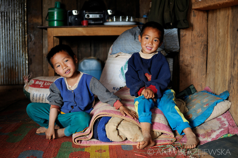 Burma/Myanmar. Two boys from Akha tribe sitting together inside the house.