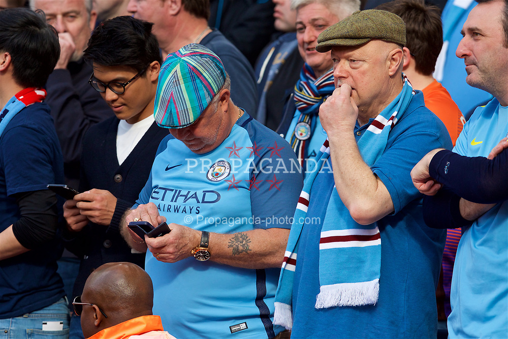 LONDON, ENGLAND - Sunday, April 2, 2017: An elderly Manchester City supporter wearing a flat cap uses his phone during the FA Premier League match against Arsenal at the Emirates Stadium. (Pic by David Rawcliffe/Propaganda)