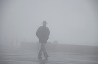 Mt. Rigi, Central Switzerland. Man walking briskly in snowy fog.