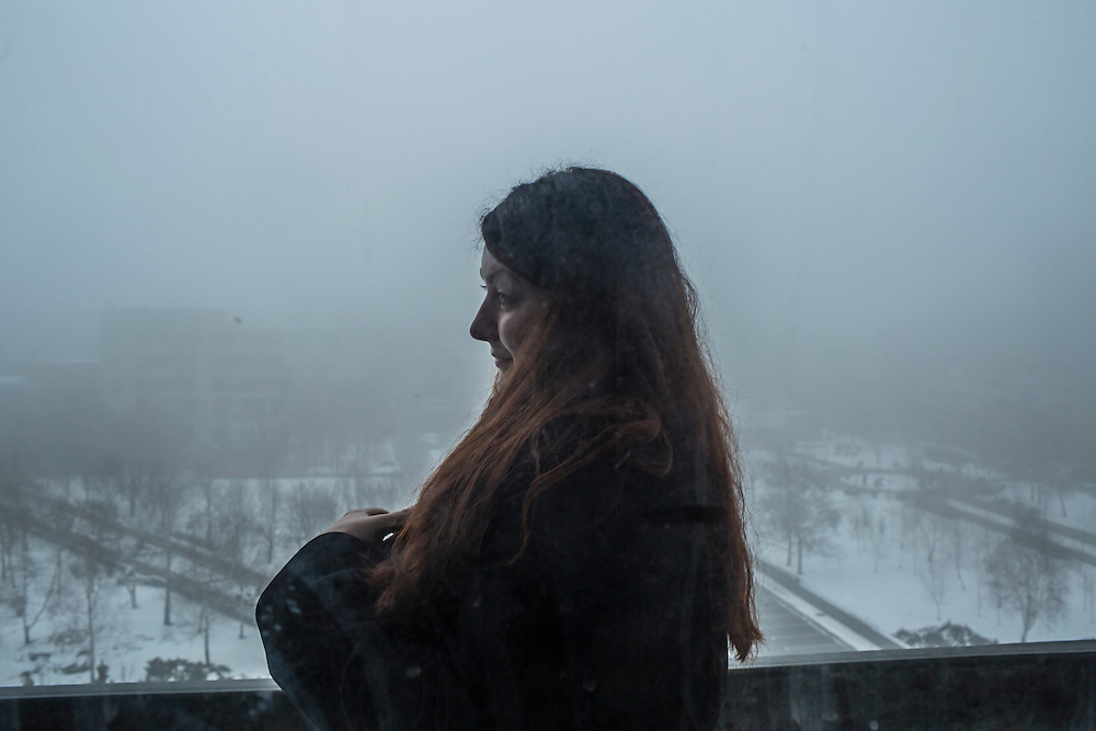A woman who works in the press center of the Donetsk People's Republic takes a cigarette break on the balcony of the administration building on Tuesday, March 22, 2016 in Donetsk, Ukraine.