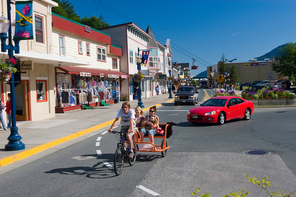 A bicycle-powered cart takes two Juneau visitors and their dog for a ride around downtown Juneau on a sunny afternoon.