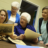 RAY VAN DUSEN/BUY AT PHOTOS.MONROECOUNTYJOURNAL.COM<br /> Retired educators from Hamilton Attendance Center, from left, Sonya Hanson, Evelyn Thompson, Judy Cockerham and Marty Perkins look through newspaper clippings as they sort out historical pieces at the Hamilton Library. The four are part of a new group aimed at enriching their community.