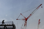 Workmen in front of cranes at the construction site for the new main stadium for the 2020 Tokyo Olympics in Gaiemmae, Tokyo, Japan Tuesday June 26th 2018