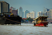"17 NOVEMBER 2012 - BANGKOK, THAILAND:  Tug boats pull barges up the Chao Phrya River in Bangkok. Bangkok used to be known as the ""Venice of the East"" because of the number of waterways the criss crossed the city. Now most of the waterways have been filled in but boats and ships still play an important role in daily life in Bangkok. Thousands of people commute to work daily on the Chao Phraya Express Boats and fast boats that ply Khlong Saen Saeb or use boats to get around on the canals on the Thonburi side of the river. Boats are used to haul commodities through the city to deep water ports for export.    PHOTO BY JACK KURTZ"