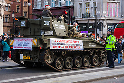 "London, December 20th 2014. Tens of thousands of shoppers descend on central London to scoop up pre-Christmas bargains as retailers offer discount incentives on ""Panic Saturday"". PICTURED: A policeman talks with a tank driver on Regents Street."