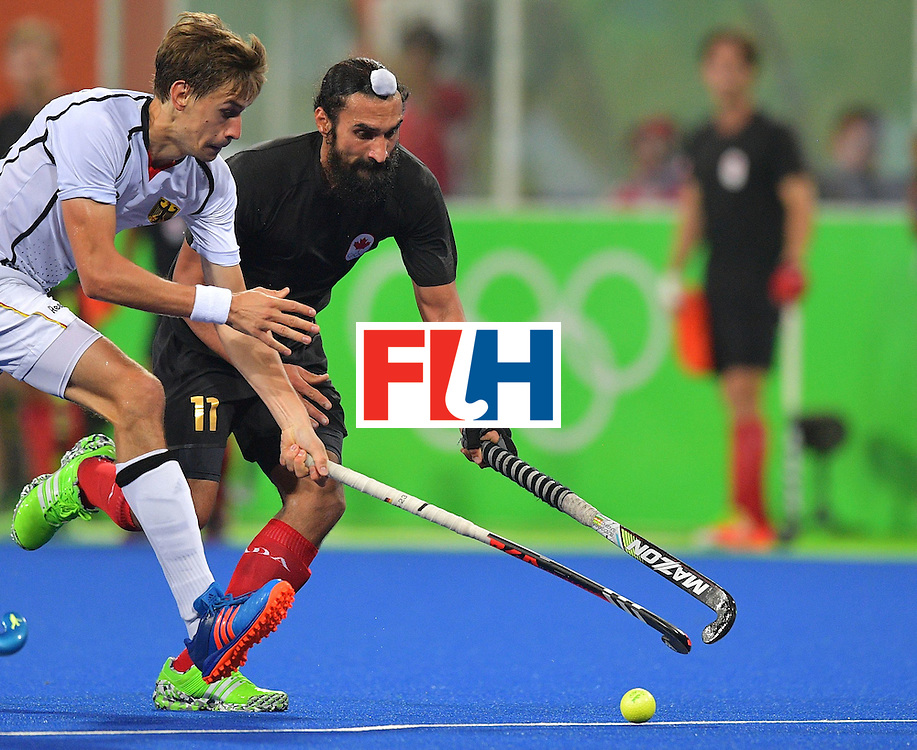 Germany's Florian Fuchs fights for the ball with Canada's Jagdish Gill (R) during the men's field hockey Canada vs Germany match of the Rio 2016 Olympics Games at the Olympic Hockey Centre in Rio de Janeiro on August, 6 2016. / AFP / Carl DE SOUZA        (Photo credit should read CARL DE SOUZA/AFP/Getty Images)