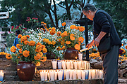 An elderly woman lights candles on the decorated gravesite of a family member for the Day of the Dead festival October 31, 2017 in Tzintzuntzan, Michoacan, Mexico.